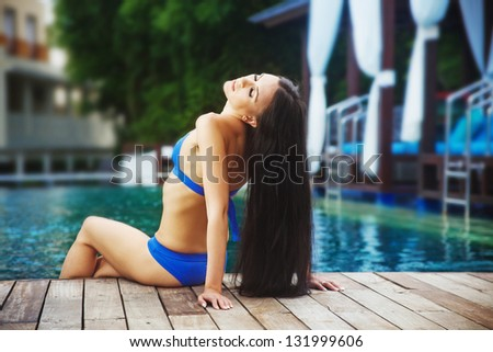 woman and swimming pool at resort (soft focus on eyes) - stock photo