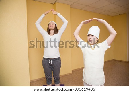 Woman and teen girl doing yoga exercise in gym on background