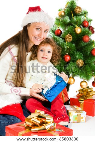 Woman and toddler girl sitting beside Christmas tree