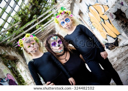 Woman and twin sisters with sugar skull makeup in abandoned house - stock photo