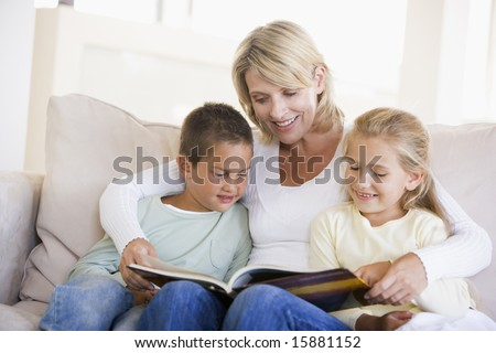 Woman and two children sitting in living room reading book and smiling - stock photo
