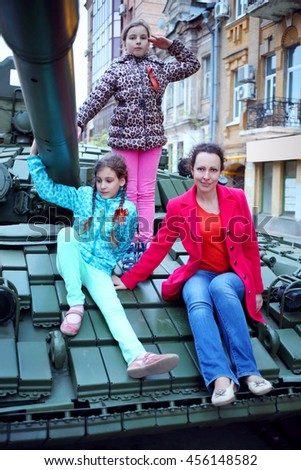 Woman and two girls pose on big armored tank in Samara during military parade, Russia - stock photo