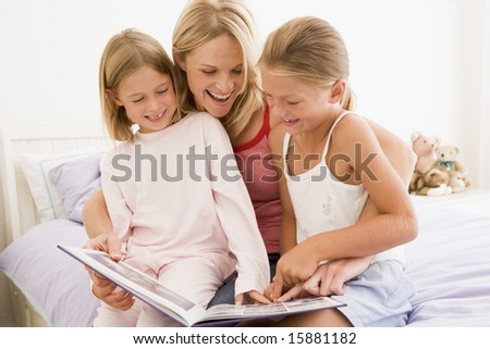 Woman and two young girls in bedroom reading book and smiling - stock photo