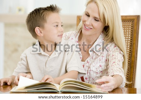 Woman and young boy reading book in dining room smiling - stock photo