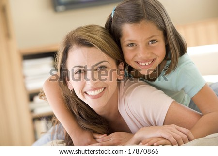 Woman and young girl in living room smiling