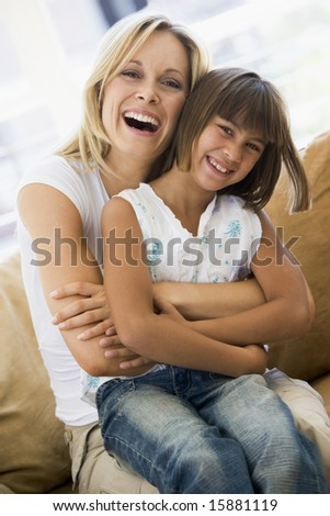 Woman and young girl sitting in living room smiling - stock photo