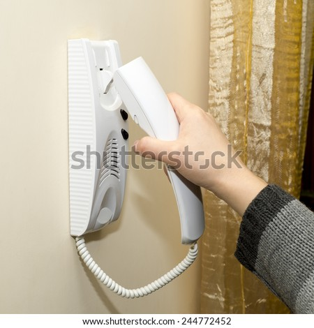 Woman answering a security  intercom - stock photo