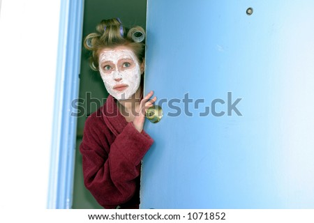 Woman answering door unprepared - stock photo