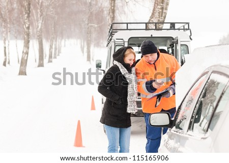 Woman answering inquiry broken car snow mechanic assistance road winter - stock photo