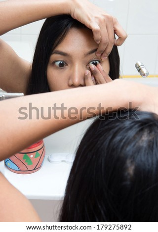 woman applying contact lens at bathroom