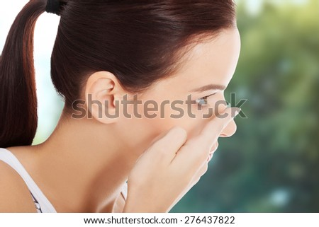 Woman applying contact lens in her eye. - stock photo