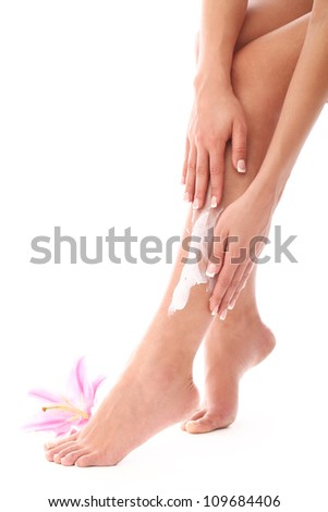Woman applying cream on her legs over white background - stock photo