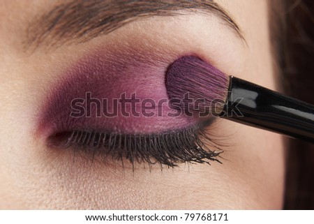 woman applying eye make-up with brush on white background - stock photo