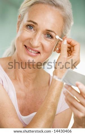 Woman applying eye makeup and smiling - stock photo
