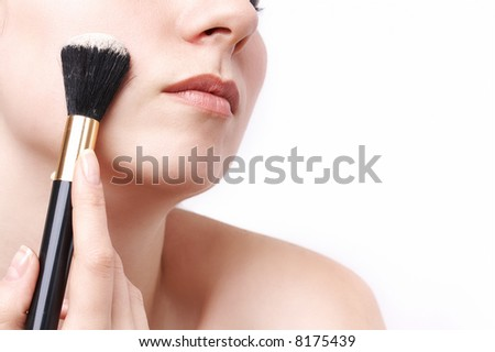 woman applying loose powder with thick black brush - stock photo
