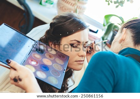 Woman applying make up for a bride in her wedding day near mirror. Closeup of a makeup artist applying makeup - stock photo