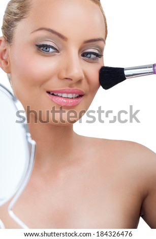 Woman applying make-up, looking in mirror - stock photo