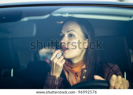 Woman applying makeup while driving - stock photo