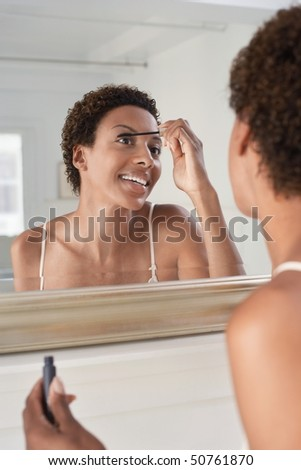 Woman applying mascara in mirror, at home