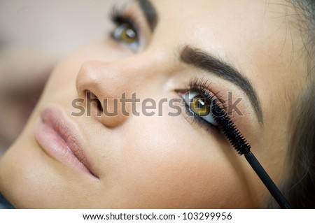 Woman applying mascara on her long eyelashes - stock photo