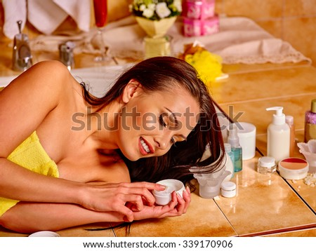 Woman applying moisturizing cream and relaxing at home luxury bath.