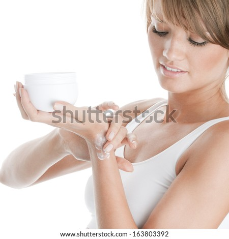 Woman applying ointment on her wrist - stock photo