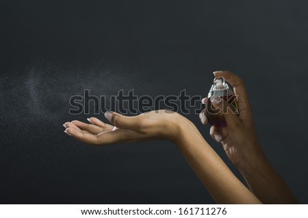 Woman applying perfume on her hand - stock photo