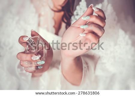 woman applying perfume on her wrist - stock photo