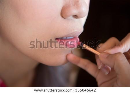 Woman applying red lipstick. Close-up view on face