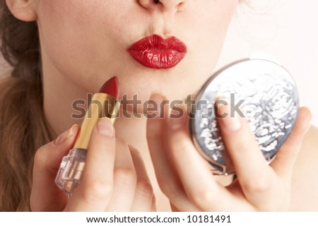 woman applying red lipstick looking in the mirror - stock photo