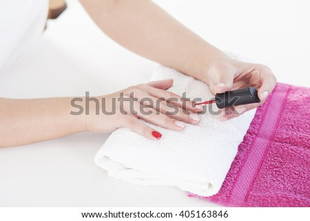 Woman applying red nail varnish to finger nails. Manicure