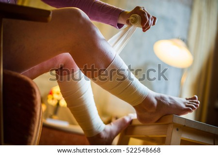 Woman applying roll bandage on her feet to cure varicose veins