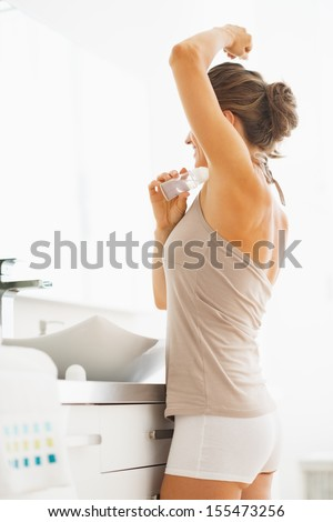 Woman applying roller deodorant on underarm in bathroom - stock photo