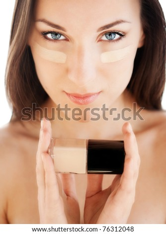 Woman applying skin foundation and holding jar of foundation on white background.
