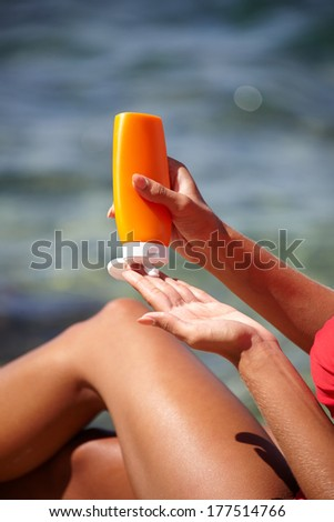 woman applying sun protection lotion  - stock photo