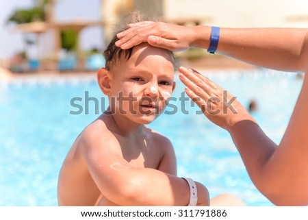Woman applying sunscreen to the face of her young son as he sits waiting to go swimming alongside a swimming pool, close up of him looking at the camera - stock photo