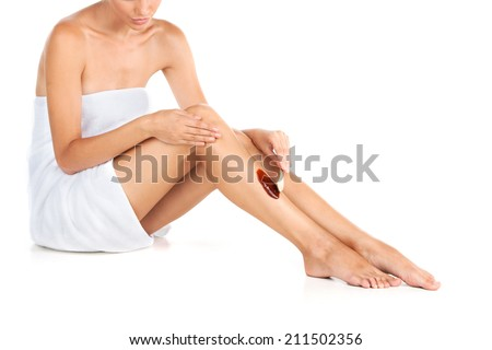 Woman applying wax to remove hair over white background. Beautiful girl applying wax to her skin  - stock photo