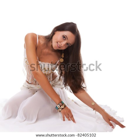 woman arabic belly dancer in white costume sitting on the floor isolated on white background - stock photo