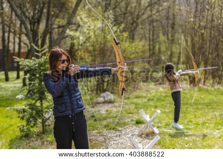 woman archer shooting with his bow at an outdoor archery range - stock photo