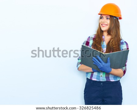 Woman architect hold open book. Smiling girl portrait against white wall.  Woman worker builder in uniform. - stock photo