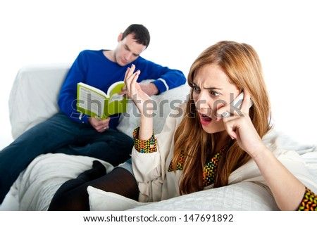 Woman arguing on a phone whilst a man reads in the background  - stock photo