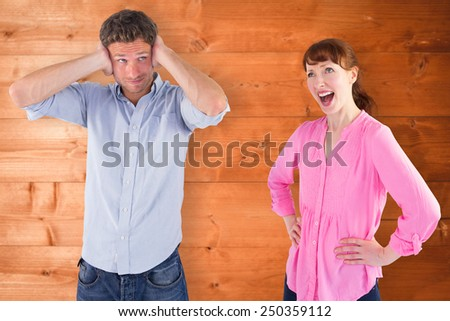 Woman arguing with ignoring man against overhead of wooden planks - stock photo