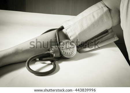 Woman arm checking blood pressure,Monochrome filtered. - stock photo
