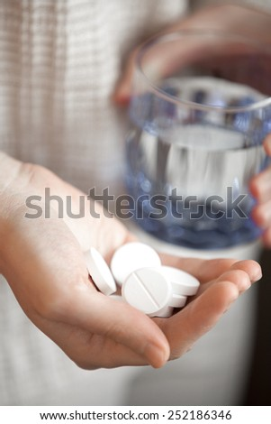 woman arm holding heap of big round meds and glass of water, shallow depth of field, focus on medicine - stock photo