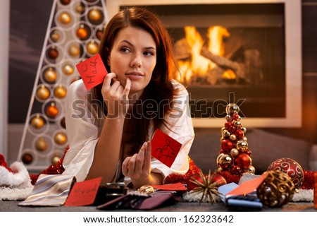 Woman arranging christmas gifts by fireplace, holding gift tag with male names, thinking, smiling, looking aside. - stock photo