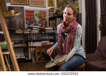 Woman artist sitting looking at her canvas in a studio with a paint brush and palette in her hand - stock photo