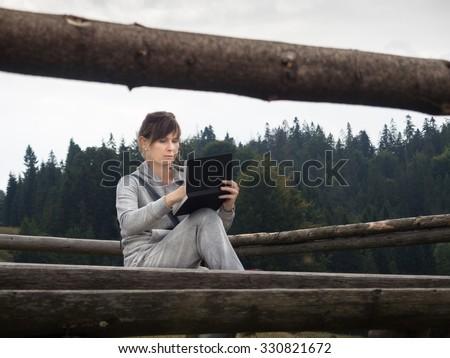 Woman artist working en plein air in mountains. - stock photo