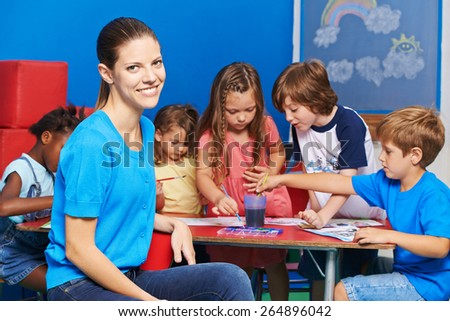 Woman as nursery teacher in kindergarten with group of children painting at table - stock photo