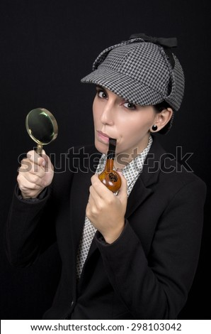 Woman as Sherlock Holmes following tracks with magnifying glass - stock photo