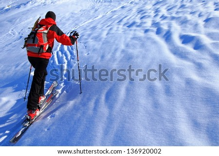 Woman ascending above clouds during ski touring in the mountains, Romania - stock photo